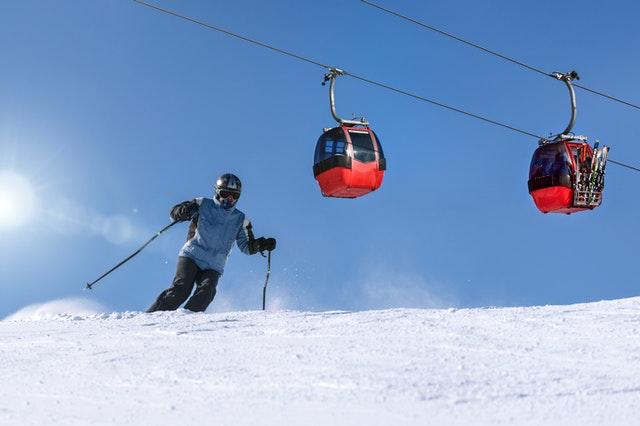 Skieur dans les Alpes avec téléphérique en fond